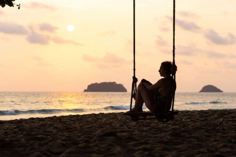 ein einsames Mädchen, das auf einer Schaukel am Strand schwingt(1)