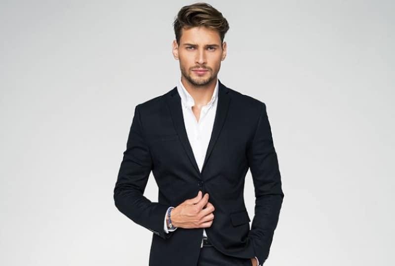 ein ernster Mann in einem Anzug, der vor einem grauen Hintergrund aufwirft(1)