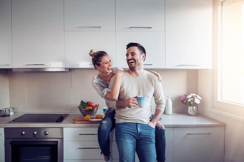 ein lächelnder Mann in den Armen seiner Frau
