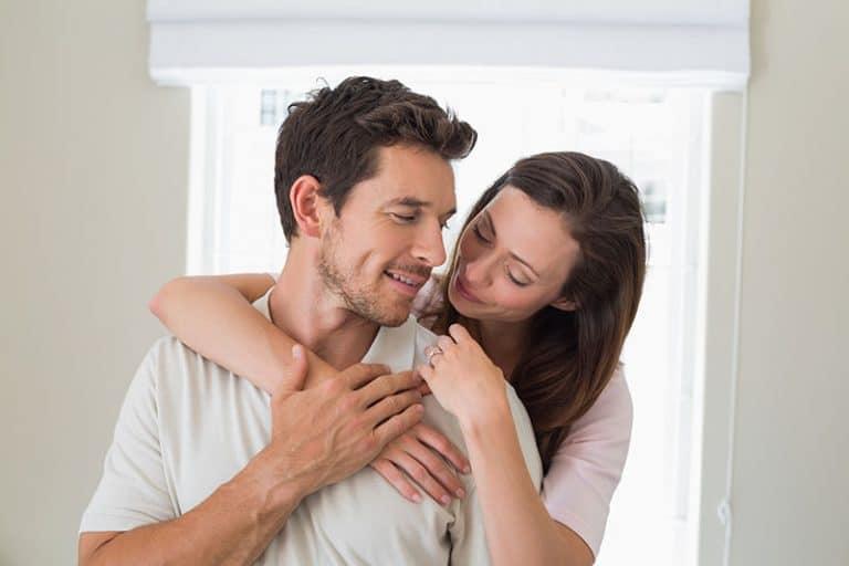 ein lächelndes Paar, das sich im Haus umarmt