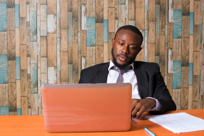 ein schwarzer Mann, der an einem Laptop arbeitet