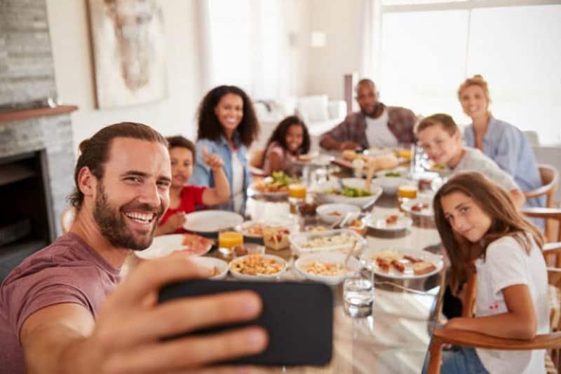 eine Familie, die zum Mittagessen ein Selfie macht