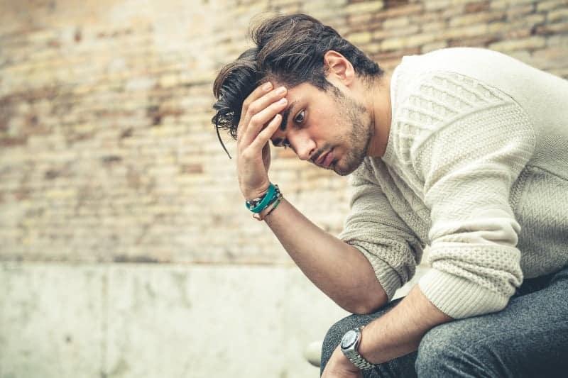 gestresster Mann sitzt an der Wand