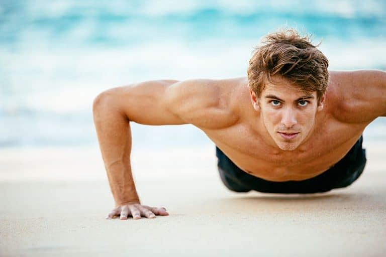muskulöser Mann, der am Strand trainiert