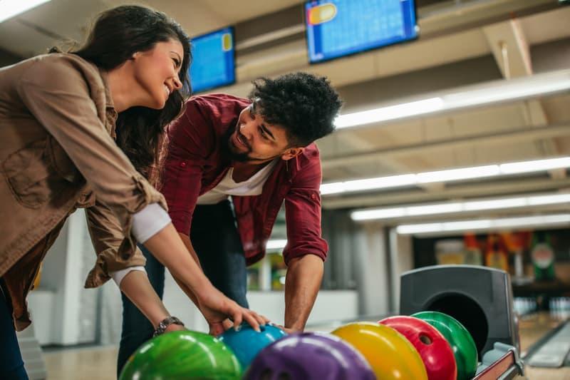 young couple choosing bowling balls