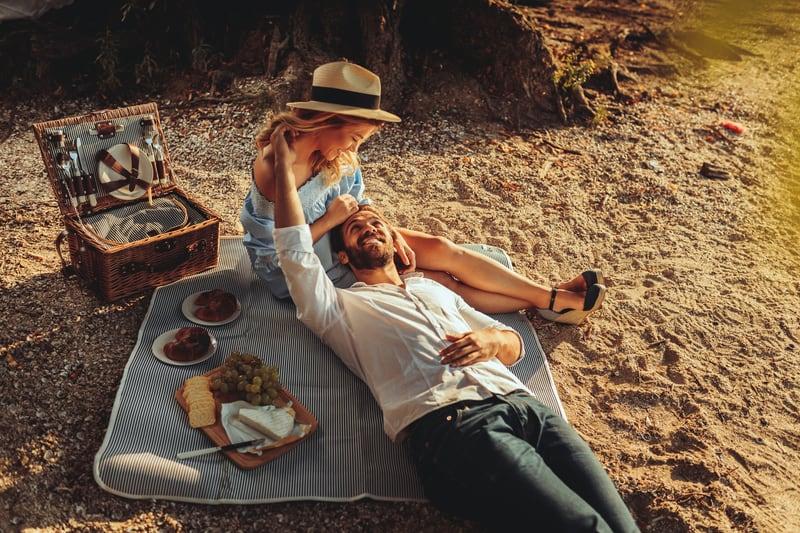 Beautiful couple enjoying picnic time on the sunset