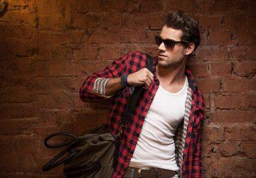 Ein gutaussehender Mann in einem gestreiften Hemd und einer Sonnenbrille mit einer Tasche auf der Schulter
