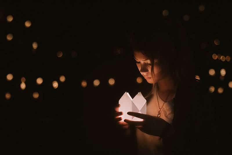 Abends steht eine Frau draußen und hält eine leuchtende Schachtel in den Händen