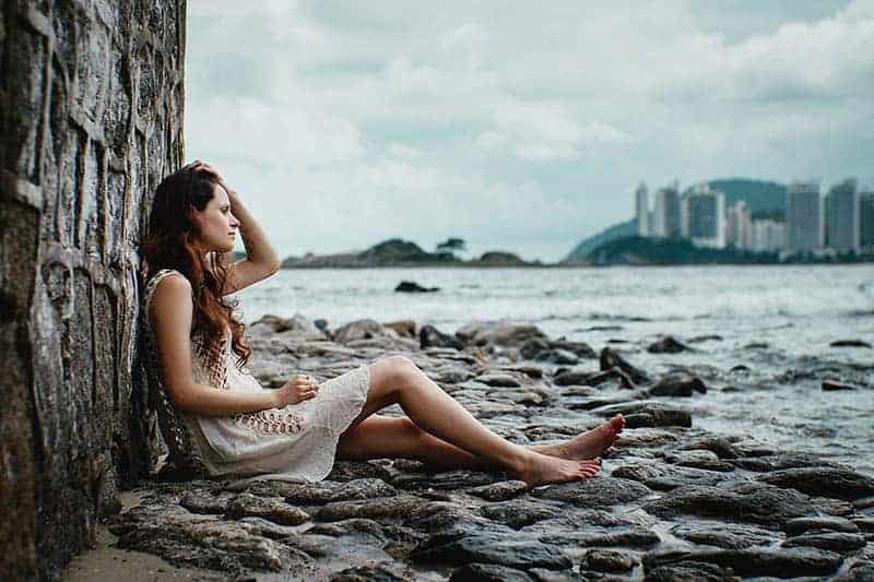 Am felsigen Ufer am Meer sitzt eine traurige Brünette in einem weißen Kleid