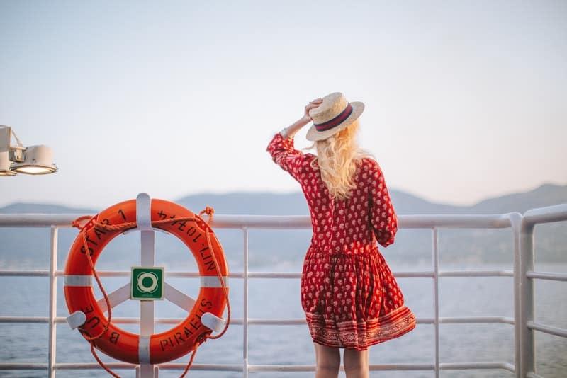 Auf dem Pier steht eine Blondine in einem roten Kleid