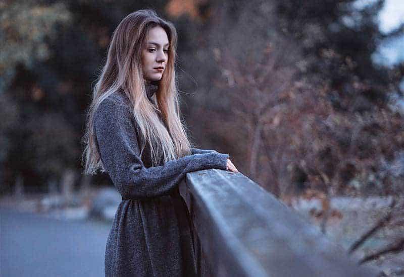 Auf der Brücke steht eine traurige Frau in einem grauen Mantel