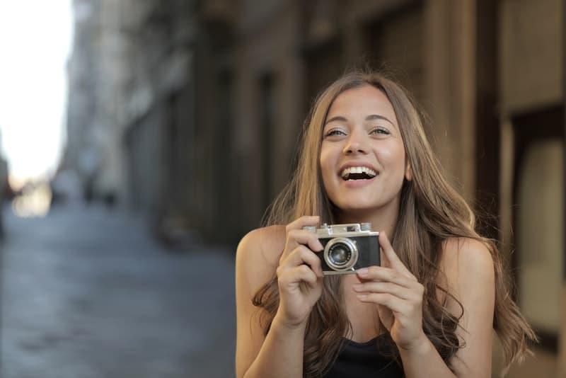 Auf der Straße steht eine lächelnde Frau mit einer Kamera in der Hand