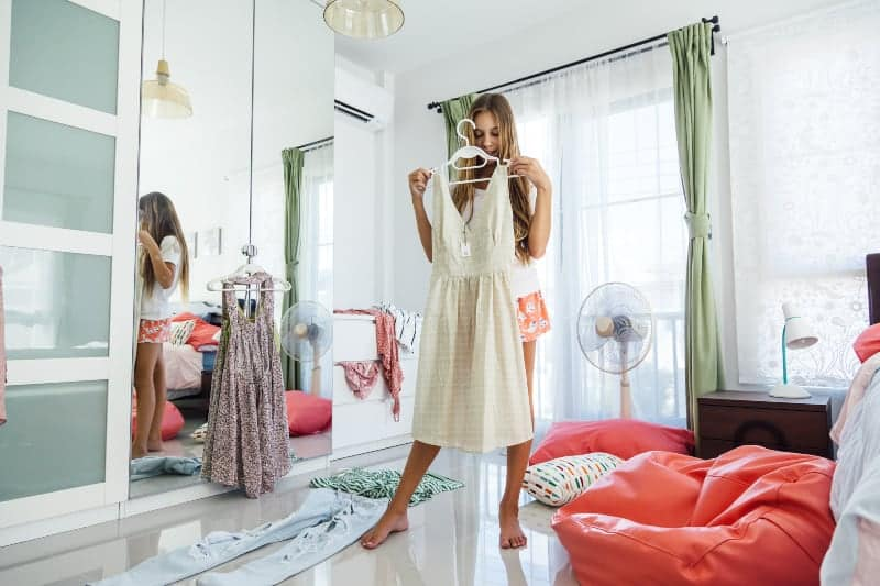 Das Mädchen in ihrem Zimmer wählt das Kleid aus