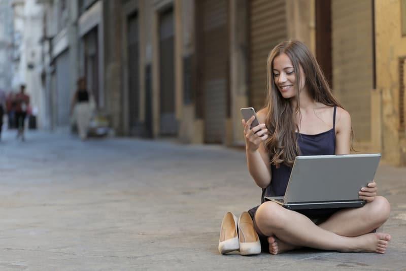 Das Mädchen sitzt auf der Straße und benutzt ein Handy und einen Laptop