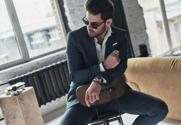 Ein gutaussehender Mann im Anzug sitzt auf einem Stuhl