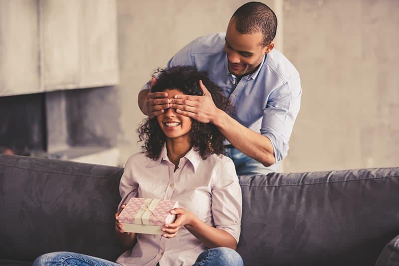 Der Mann hält die Augen seiner lächelnden Frau mit den Händen