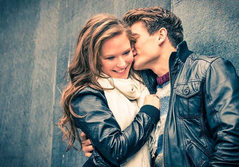 Der Mann küsst zärtlich die lächelnde Frau