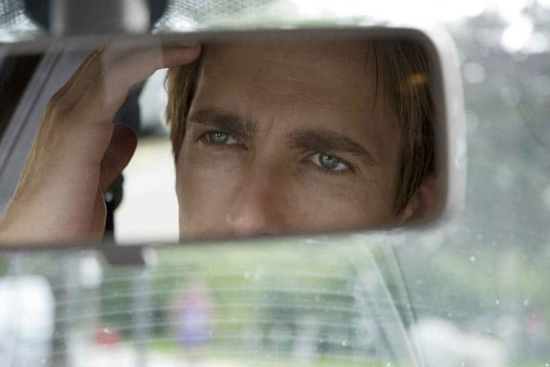 Der Mann sitzt im Auto und schaut in den Rückspiegel