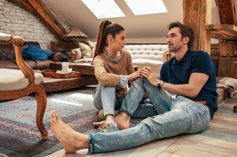 Der Mann und die Frau in der Wohnung sitzen Händchen haltend auf dem Boden