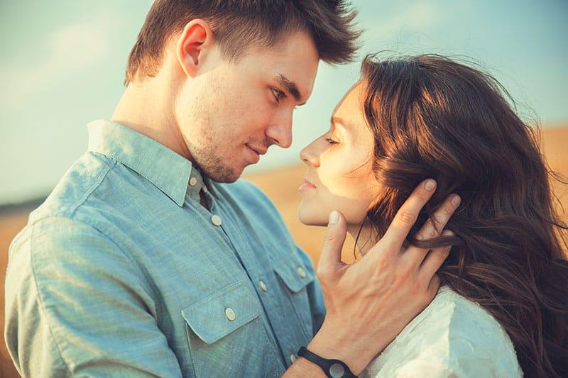 Der Mann und seine Freundin stehen auf und schauen sich in die Augen