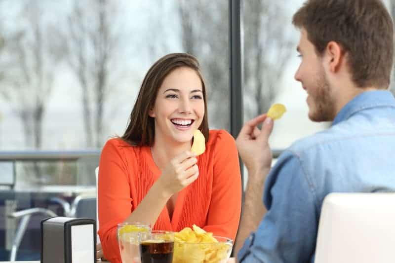Der Mann und seine lächelnde Frau sitzen und essen Pommes