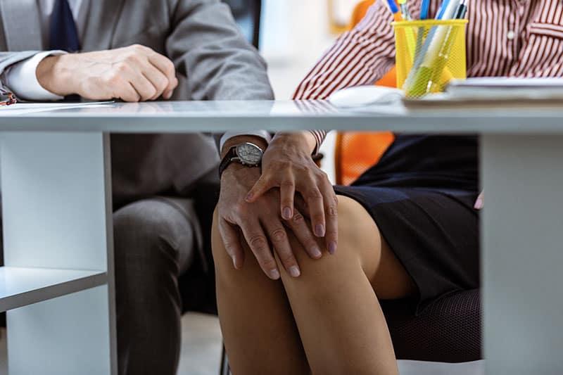 Der Mann unter dem Tisch berührt die Knie der Frau