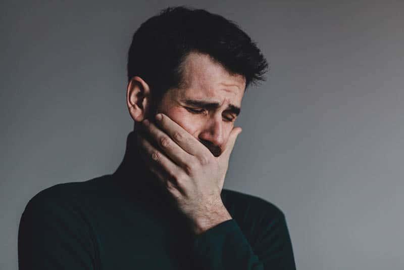 Der traurige Mann weint und hält seinen Mund