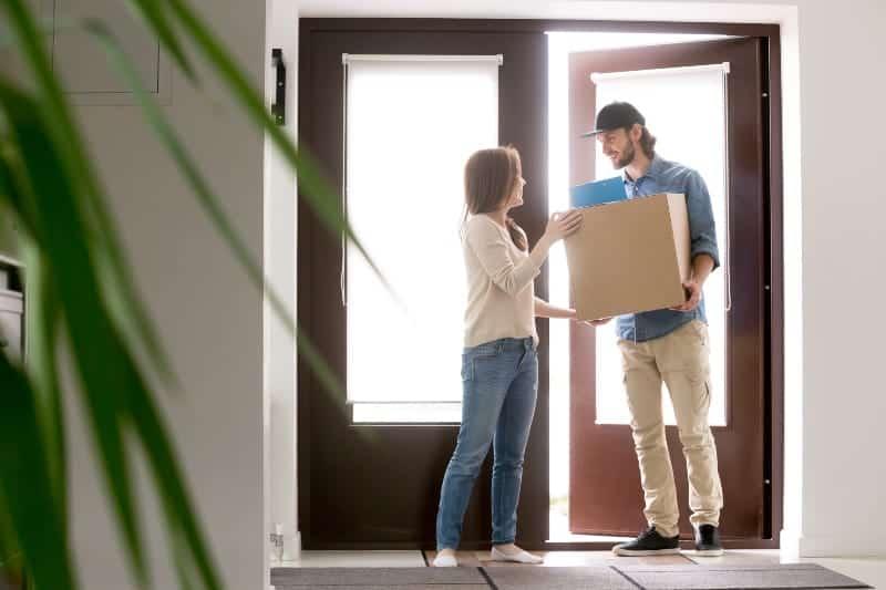 Die Frau an der Haustür nimmt dem Mann mit dem Bart ein Päckchen ab