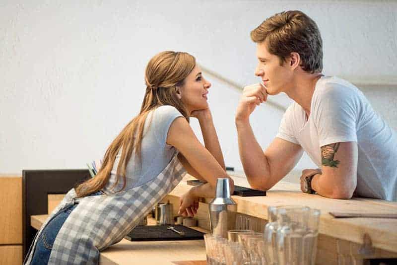 Die Frau und der Mann in der Küche flirten