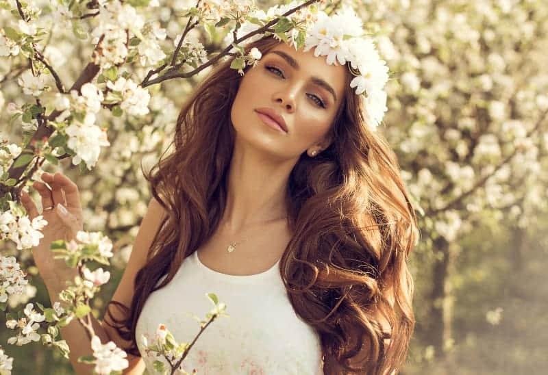 schöne Brünette mit Blumen auf Kopf posiert