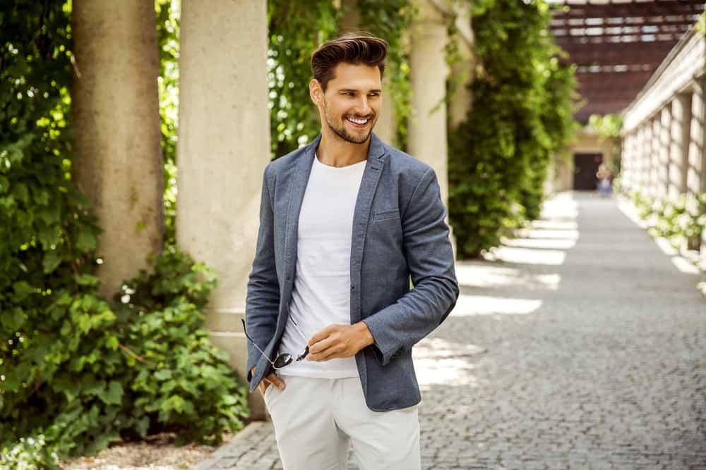 Draußen steht ein lächelnder Mann in grauer Jacke und weißer Hose