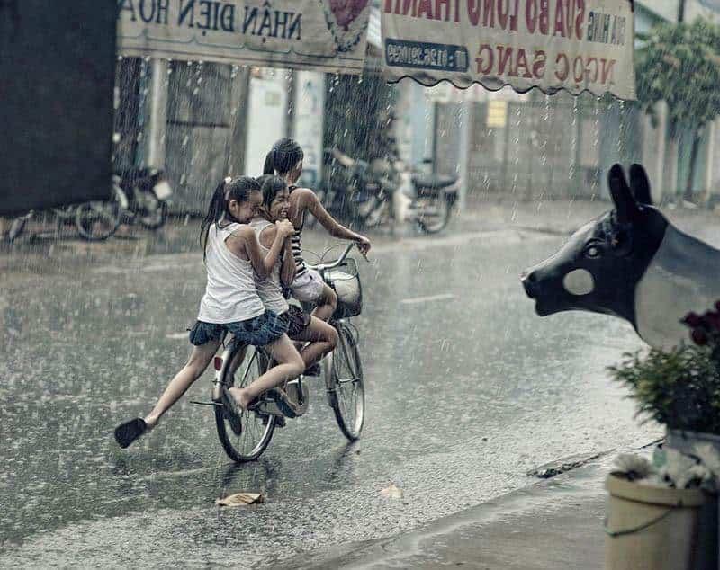 Drei junge Mädchen fahren im Regen Fahrrad