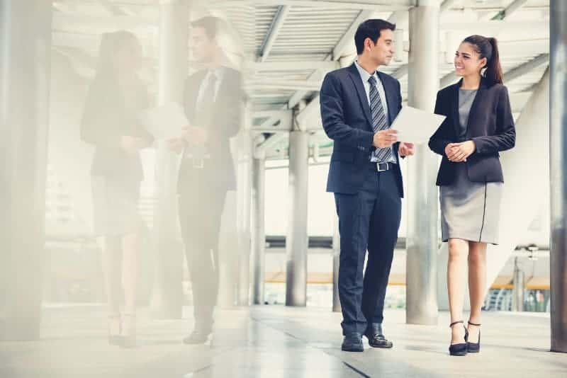 Ein Geschäftsmann mit Papieren in der Hand spricht mit einer lächelnden Frau