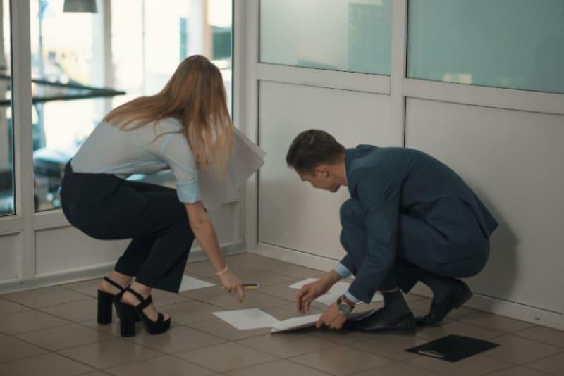 Ein Kollege hilft einem Kollegen, Papiere vom Boden aufzuheben