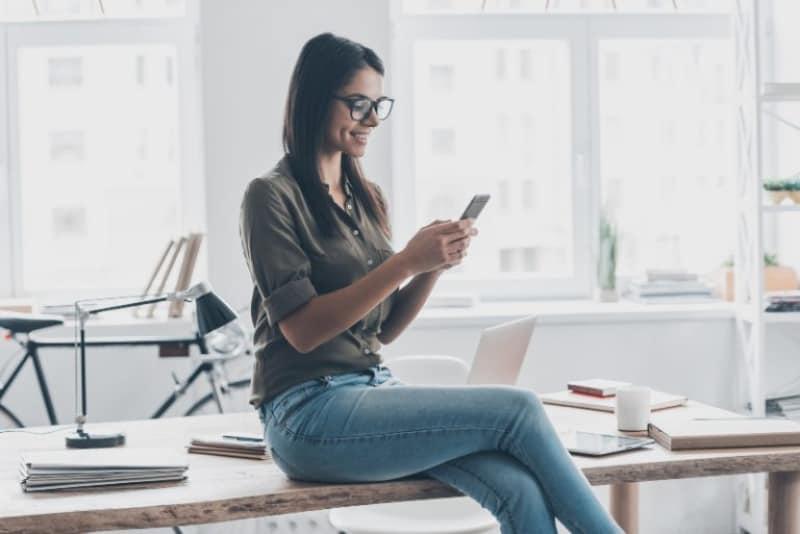 Ein Mädchen sitzt an einem Schreibtisch, hält ein Handy in den Händen und lächelt