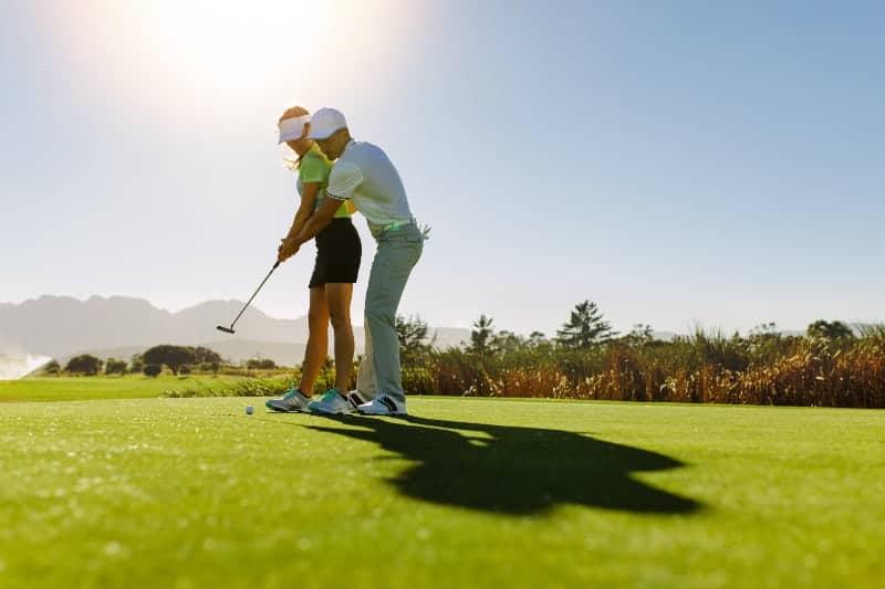 Ein Mann bringt einer Frau das Golfspielen bei