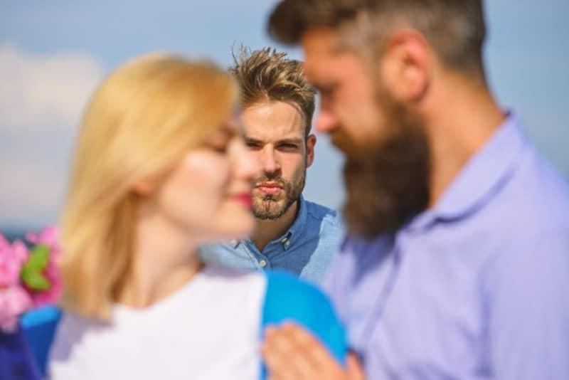 Ein Mann, der eifersüchtig auf einen Mann ist, der mit seiner Freundin spricht