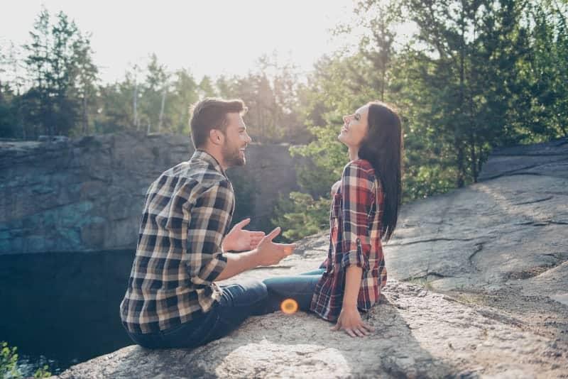 Ein Mann erzählt seiner Frau etwas Lustiges, während er auf einem Felsen in der Natur sitzt