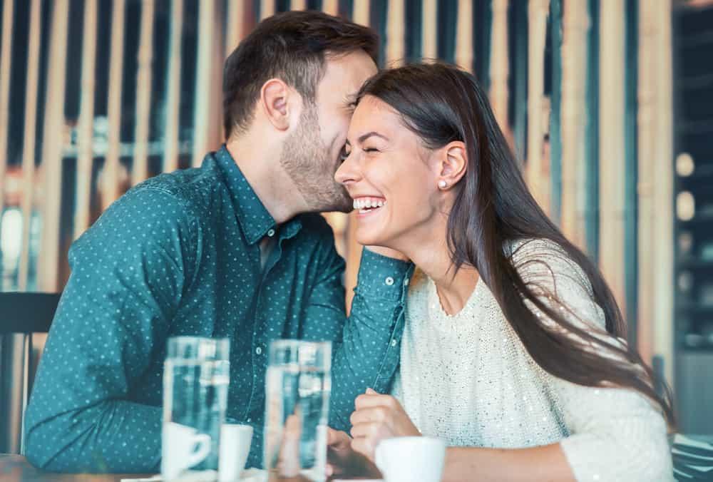 Ein Mann in einem Hemd in einem Café flüstert einer lächelnden Frau etwas ins Ohr