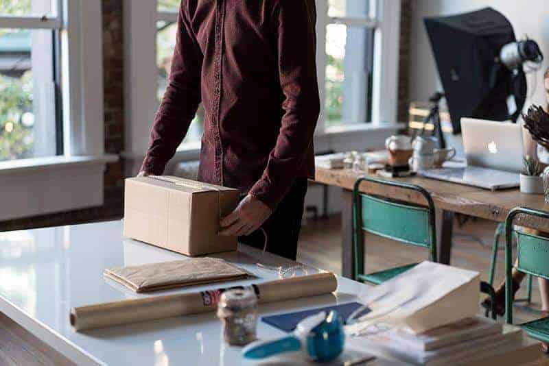 Ein Mann in einem burgunderfarbenen Hemd packt ein Paket