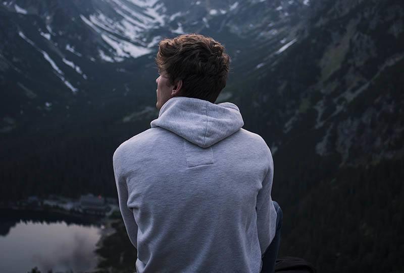 Ein Mann in einem grauen Hoodie sitzt auf einem Hügel