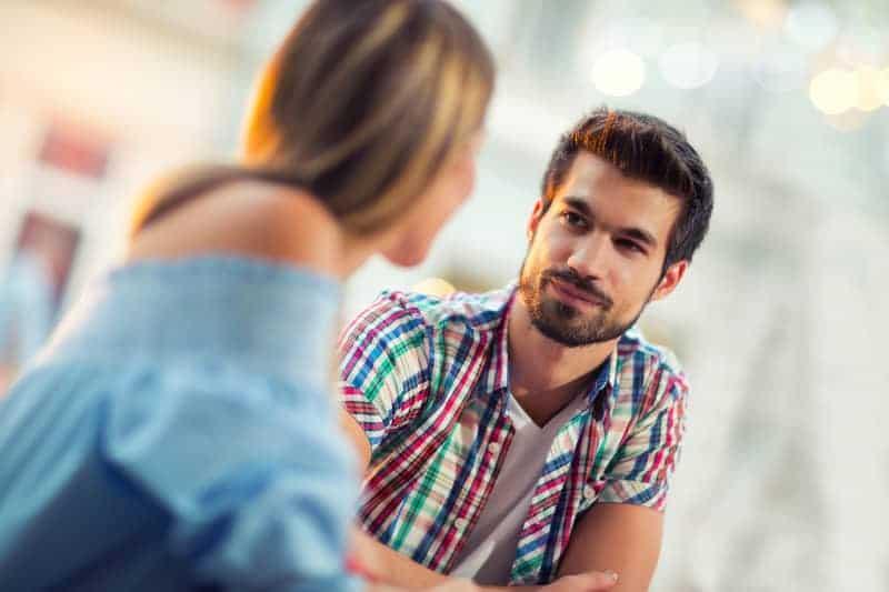 Ein Mann in einem karierten Hemd sieht seine Frau liebevoll an
