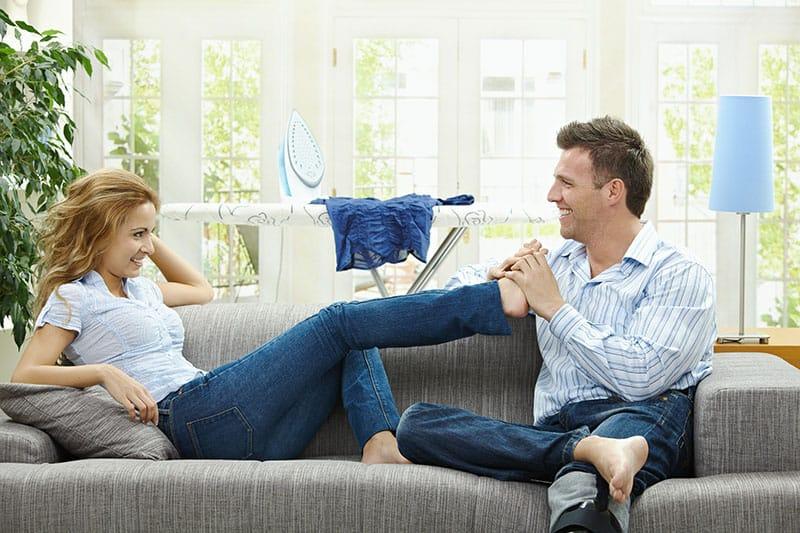 Ein Mann massiert die Füße seiner Frau