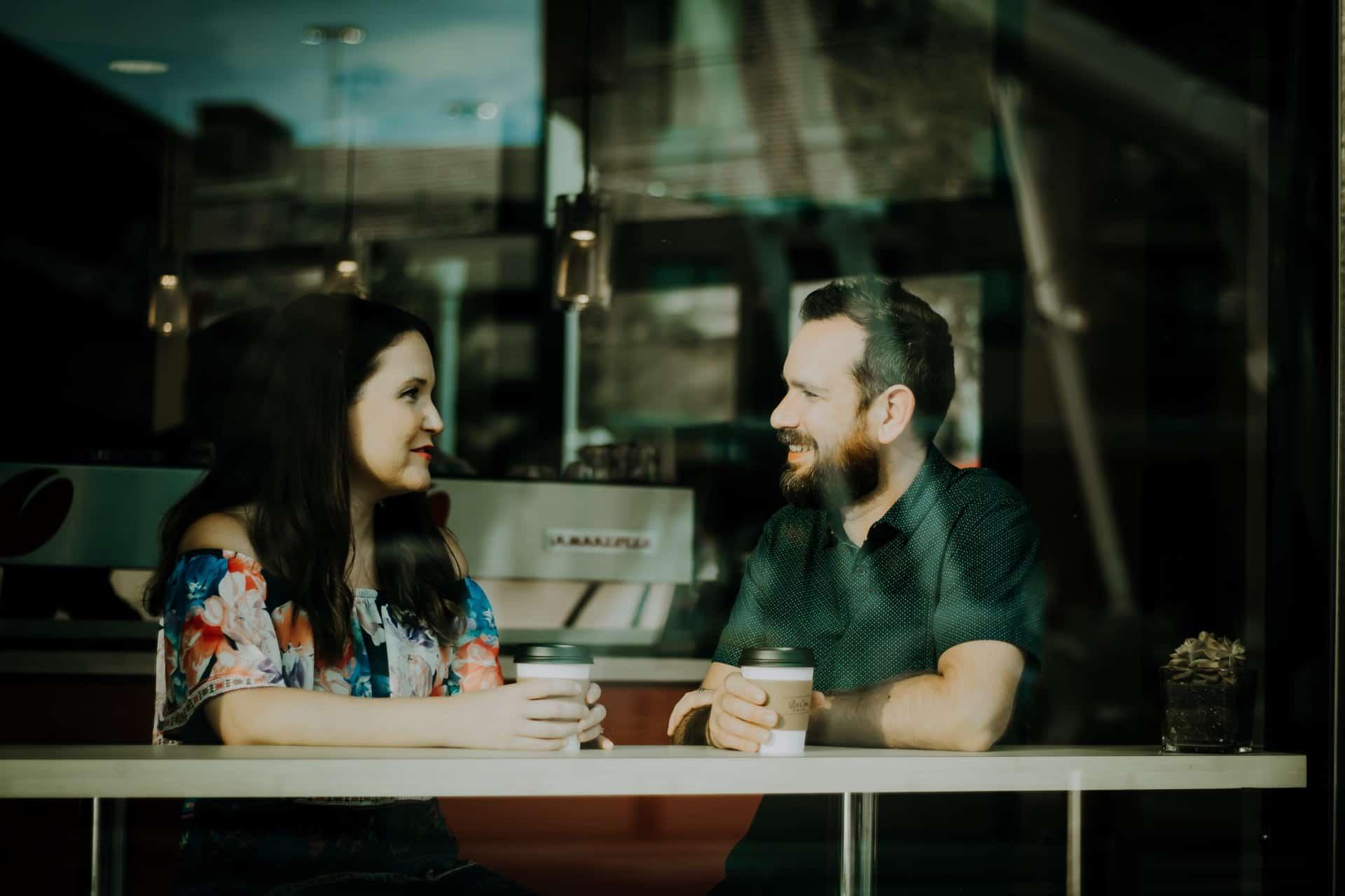 Ein Mann mit Bart und einem Lächeln, der mit einer Frau in einem Café spricht