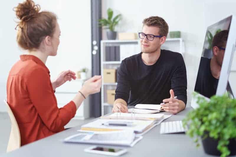 Ein Mann mit Brille und eine Frau an einem Schreibtisch sprechen über Geschäfte