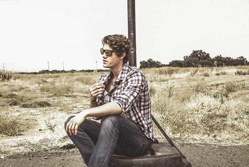 Ein Mann sitzt auf einem Reifen und lehnt sich an eine Stange