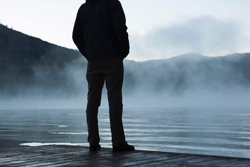 Ein Mann steht am Fluss