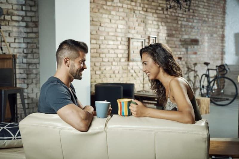 Ein Paar unterhält sich mit einem Lächeln in der Wohnung und einer Tasse Tee