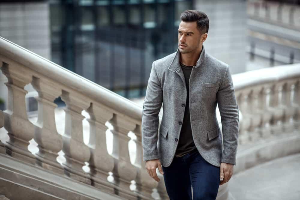 Ein gutaussehender Mann in einem grauen Mantel geht die Straße entlang