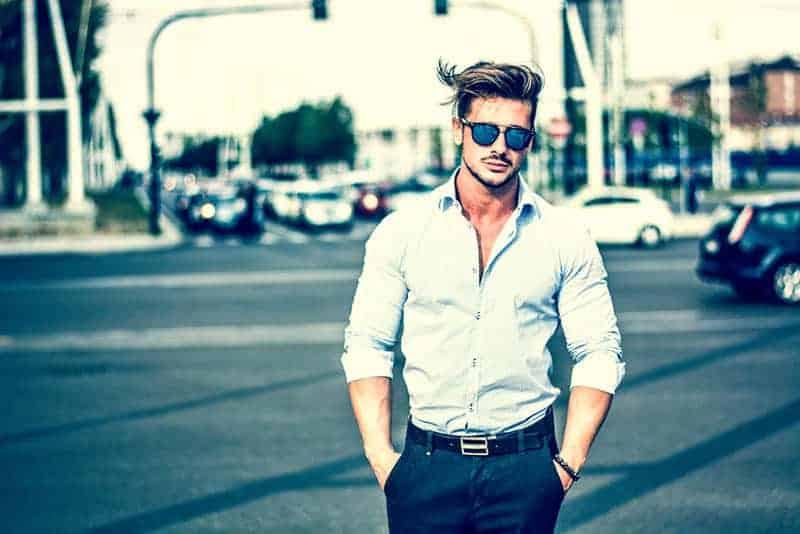 Ein gutaussehender Mann in einem weißen Hemd mit Brille geht die Straße entlang